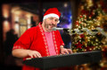 Bearded Santa Claus playing digital piano and singing Royalty Free Stock Photo