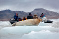 Bearded seal on blue and white ice in Arctic Svalbard, Norway, motor boat with tourists in the background Royalty Free Stock Photo