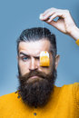 Bearded serious man with tea bag handsome long lush beard and moustache on face holding in yellow shirt in studio on blue Royalty Free Stock Photography