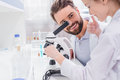 Bearded teacher looking at little student working with microscope in lab Royalty Free Stock Photo