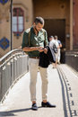 Bearded traveller chatting over his phone while standing on bridge summertime Royalty Free Stock Photos