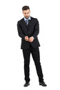 Bearded young man in suit buttoning sleeves looking down full body length portrait isolated over white studio background Royalty Free Stock Image