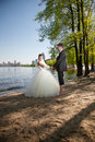 Beatiful newly married couple walking on beach near river Stock Photography