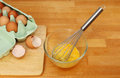 Beating eggs in a glass mixing bowl with a whisk on a wooden kitchen worktop Stock Photo