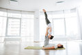 Beauiful couple practicing acro yoga on green mat Royalty Free Stock Photo