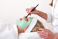 Beautician applying facial mask on the cheekbones green thalasso with a brush of a laying and relaxed beautiful blond women Royalty Free Stock Photography