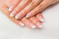 At the beautician close uo of female hands on a white towel complete french manicure beauty salon Stock Photography