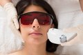 Beautician giving epilation laser treatment close up of on woman s face Royalty Free Stock Photo