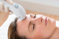 Beautician giving laser epilation treatment to woman face close up of young Royalty Free Stock Image