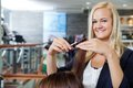 Beautician at parlor portrait of happy young female giving a haircut to female Royalty Free Stock Photography