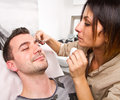 Beautician plucking a beautiful man eyebrows with tweezers in a men beauty salon Stock Photos
