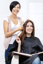 Beautician tries lock of dyed hair on the client blond sitting chair in hairdressing salon Royalty Free Stock Photography