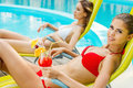 Beauties by the poolside side view of two beautiful young women in bikini drinking cocktails while relaxing in deck chair near Royalty Free Stock Photography