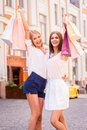 Beauties with shopping bags two attractive young women holding and smiling while standing outdoors Stock Photography