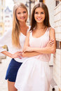 Beauties in style two beautiful young well dressed women smiling at camera while standing close to each other outdoors Royalty Free Stock Photos