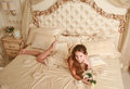 Beautiful adolescence young teenager girl with dark long hair wearing a pretty beige dress lying on a bed in a luxurious beige Stock Photography