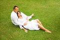 Beautiful adult couple relaxing in garden sit on the grass Stock Photo