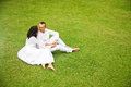 Beautiful adult couple relaxing in garden sit on the grass Royalty Free Stock Image