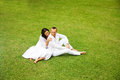 Beautiful adult couple relaxing in garden sit on the grass Royalty Free Stock Images