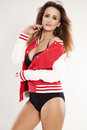 Beautiful adult sensuality woman portrait of a brunette cheerleader girl in black lingerie and red baseball jacket on white Royalty Free Stock Images