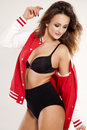 Beautiful adult sensuality woman portrait of a brunette cheerleader girl in black lingerie and red baseball jacket on white Royalty Free Stock Image