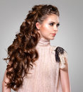 Beautiful adult woman with long brown curly hair fashion model posing at studio Royalty Free Stock Photography