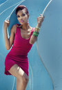 Beautiful african american model posing in pink dress against blue curve repeating pattern background Stock Images