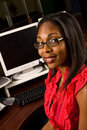 Beautiful african american receptionist wearing telephone headset glasses smiling as looks toward camera Stock Images
