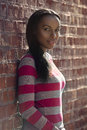 Beautiful african american student woman wearing casual clothes and standing near brick wall outdoors Royalty Free Stock Photo