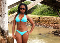 Beautiful african girl in bikini a south black is standing on the banks of the river a blue she is looking very cool with her Stock Photo