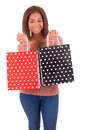 Beautiful african woman holding a credit card and shopping bags smiling isolated Stock Photos