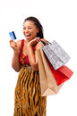 Beautiful african woman shopping laughing holding bags and a blank card on an isolated background Royalty Free Stock Image