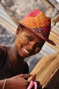 Beautiful african women from madagascar with traditional colorful hat and sun protection mask on her face many in Stock Image