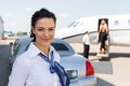 Beautiful airhostess standing against limousine portrait of and private jet at airport terminal Stock Photography