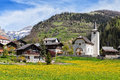 Beautiful Alpine landscape with church and typical Swiss houses at spring sunny day , Inden village , canton of Valais , Switze Royalty Free Stock Photo