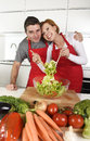 Beautiful American couple working at home kitchen in apron mixing vegetable salad smiling happy Royalty Free Stock Photo