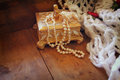 A beautiful antique golden jewelry box with natural white pearls on wooden table Royalty Free Stock Photo