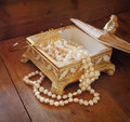 A beautiful antique golden jewelry box with natural white pearls on wooden table. retro filtered image Royalty Free Stock Photo