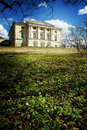 A beautiful antique yellow mansion stands on a hill in the park, in the foreground there are spring flowers blossoming Royalty Free Stock Photo