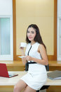 Beautiful asian business woman holding coffee cup at her desk in office Stock Photo