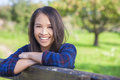 Beautiful asian eurasian girl resting on fence happy young woman or wearing denim shirt smiling and leaning in sunshine Royalty Free Stock Photography