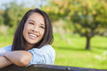 Beautiful asian eurasian girl smiling with perfect teeth happy young woman or wearing denim shirt and leaning on fence in sunshine Royalty Free Stock Image