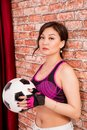 Beautiful Asian girl with a ball for playing football. Royalty Free Stock Photo