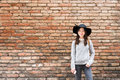 Beautiful asian girl in fashionable dress, standing in front of red brick wall background with copy space Royalty Free Stock Photo