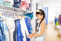 Beautiful asian girl with flower accessory in shop hair choosing clothes the clothing store Royalty Free Stock Image