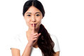 Beautiful asian girl gesturing silence casual instructing to be silent Royalty Free Stock Photo