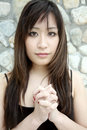 Beautiful Asian girl with hands clasped Royalty Free Stock Image