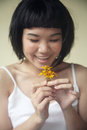 Beautiful asian girl holding flowers in white Royalty Free Stock Photo