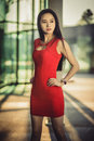 Beautiful Asian girl model in red dress posing at the modern glass style city background. Sunny day.