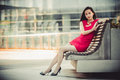 Beautiful Asian girl model in red dress sitting on a bench posing at the modern city background. Royalty Free Stock Photo